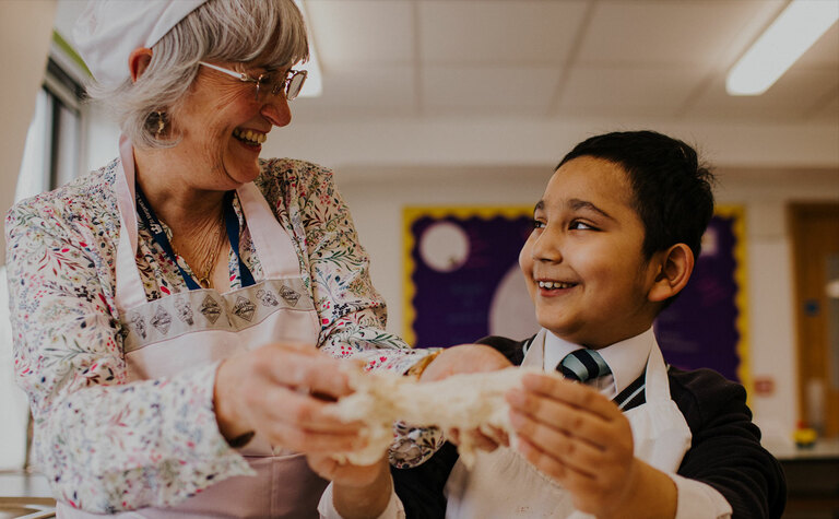 Member of teaching staff enjoying cookery lesson with junior school pupil