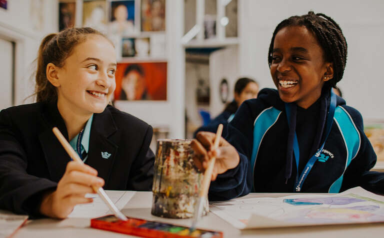 Two senior school pupils smiling and painting at St Margaret's School Bushey