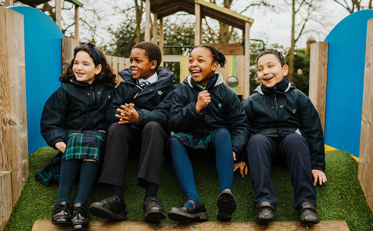 A group of Junior School pupils sitting and laughing in play area outside St Margaret's School Bushey