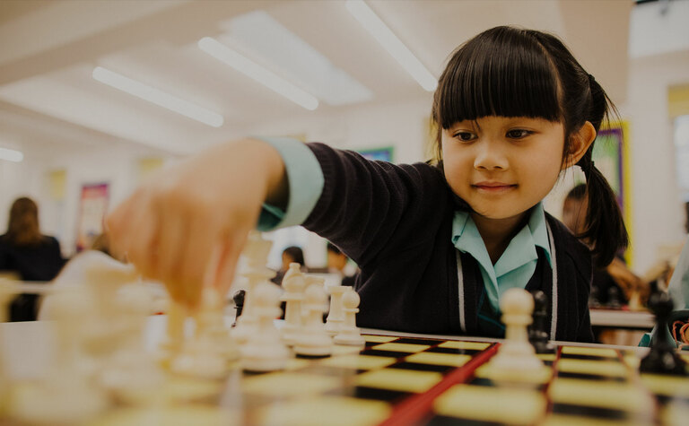 Lower junior school girl playing chess during co-curricular session at St Margaret's School
