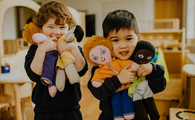 Two nursery school pupils happily cuddling soft toy dolls in the nursery at St Margaret's