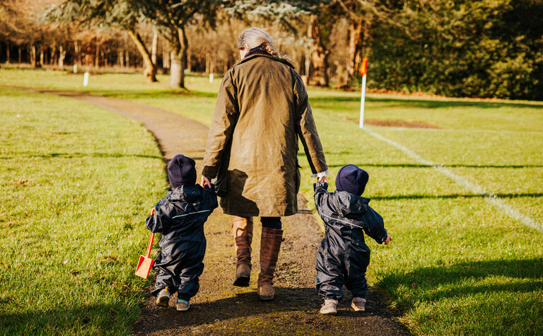 Staff member and two children taking a walk outside the Nursery at St Margaret's School Bushey