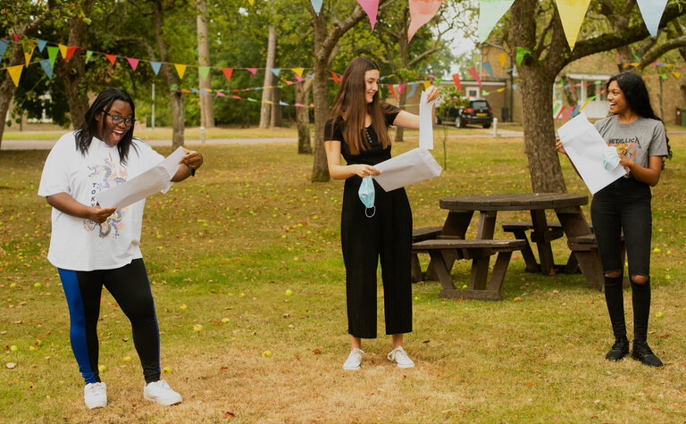 Three excited students opening their exam results outside St Margaret's School Bushey