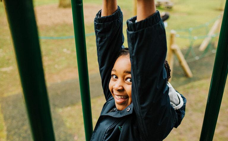 St Margaret's junior school girl smiling and swinging in playground