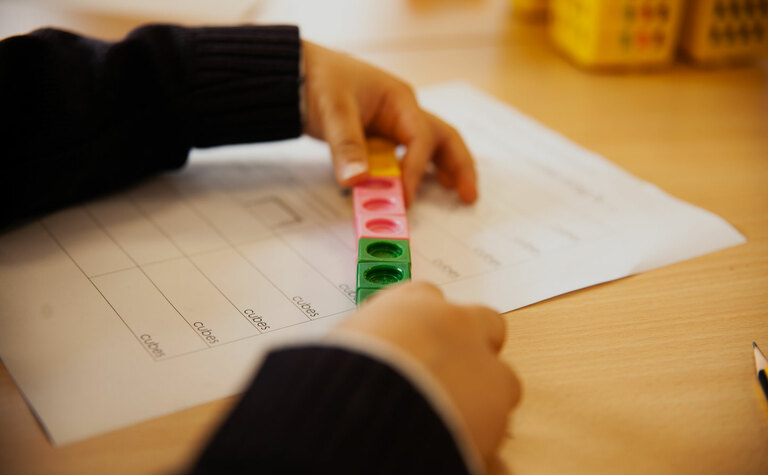 Close up of lower junior school pupil's hands with mathematical cubes learning in classroom