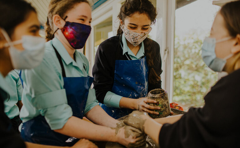 Senior school pupils laughing and enjoying pottery lesson at St Margaret's School