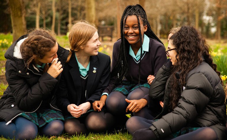 Group of senior school students sitting on grass talking and laughing outside St Margaret's School