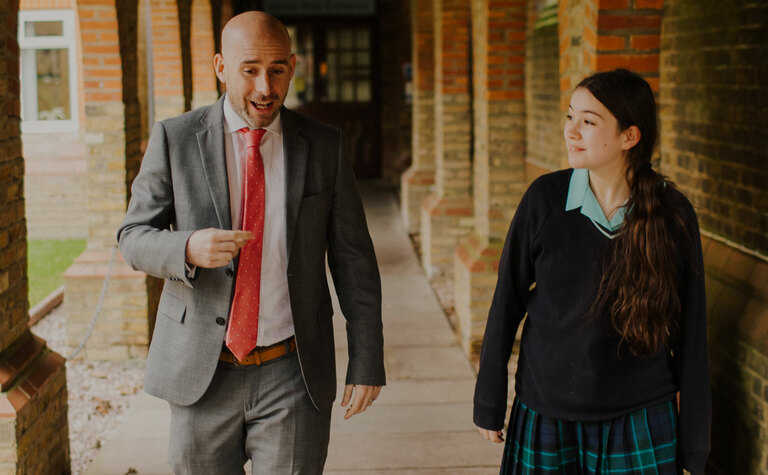 Senior school pupil walking and talking with St Margaret's School staff member