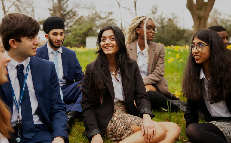 Group of sixth form students sat together on grass outside at St Margaret's School Bushey