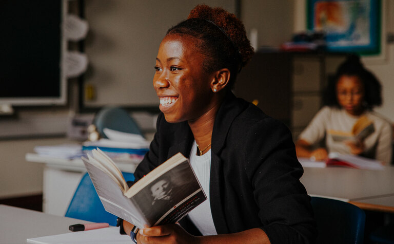 Smiling sixth form girl reading book in classroom at St Margaret's School Bushey