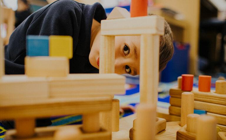 Nursery pupil peeking through wooden building blocks following the EYFS curriculum at St Margaret's School Bushey