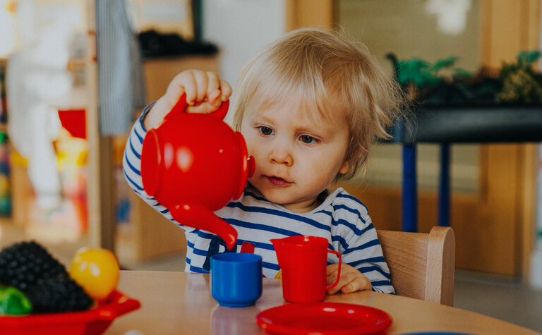 Nursery child pretending to pour tea at a tea party during after school care at St Margaret's School Bushey