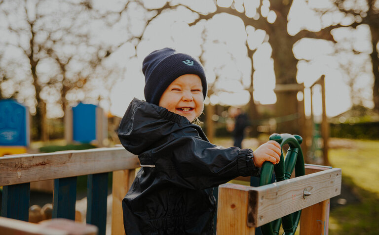 Nursery pupil with a very happy smile playing and exploring the playground area outside at St Margaret's School Bushey