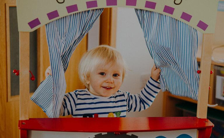 Nursery age child playing peek-a-boo in play area at St Margaret's School Bushey Nursery