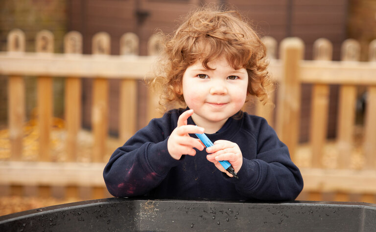 St Margaret's School Nursery  child playing outside with a water tray in the Early Years play area