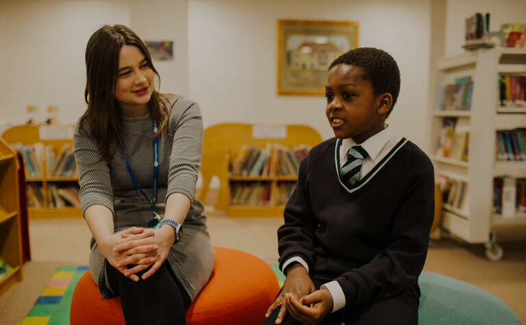 Upper junior school pupil sitting in library talking with a teacher at St Margaret's School