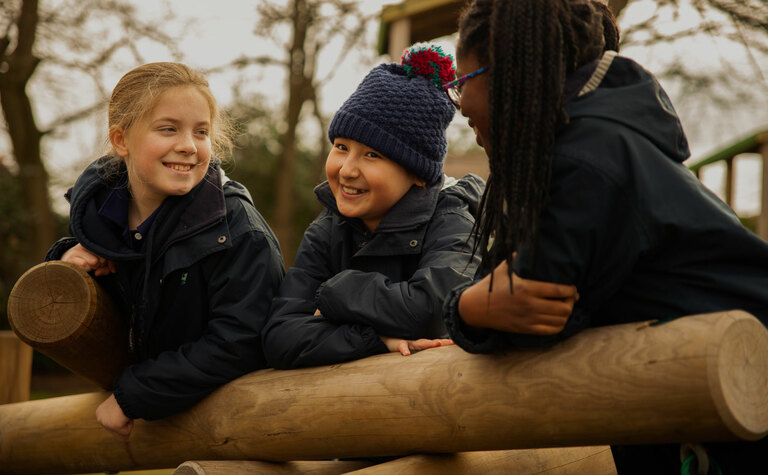 Three junior school pupils playing and having fun in the outdoor play area at St Margaret's School Bushey