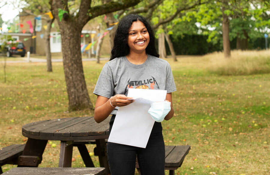 St Margarets School A level Student opening exam results envelope in orchard on results day 2020