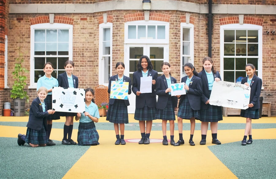 Group of Year 6 pupils outside Junior School holding examples of work