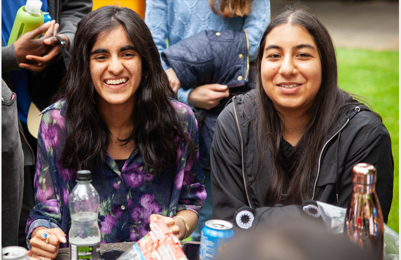 Two of St Margarets School Y13 Leavers laughing at party in orchard