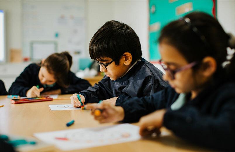 Junior school pupils working in classroom at co-educational school St Margaret's