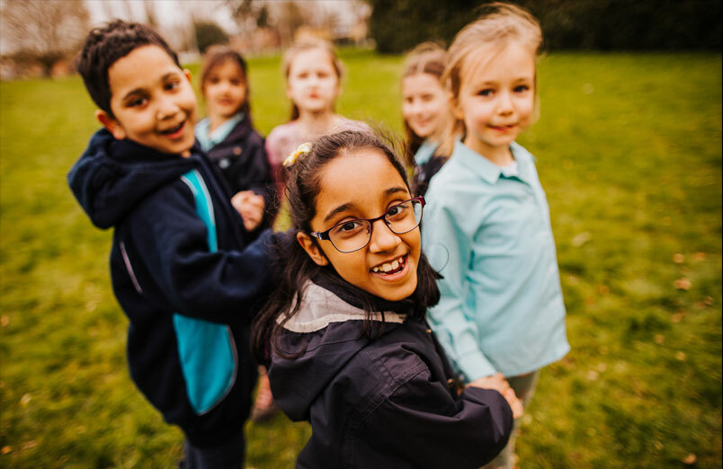 Junior school pupils playing outside at St Margaret's co-educational school in Bushey
