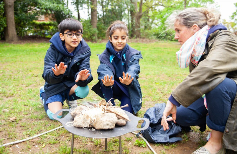 St Margarets School Outdoor Education lesson with two children and teacher round fire pit