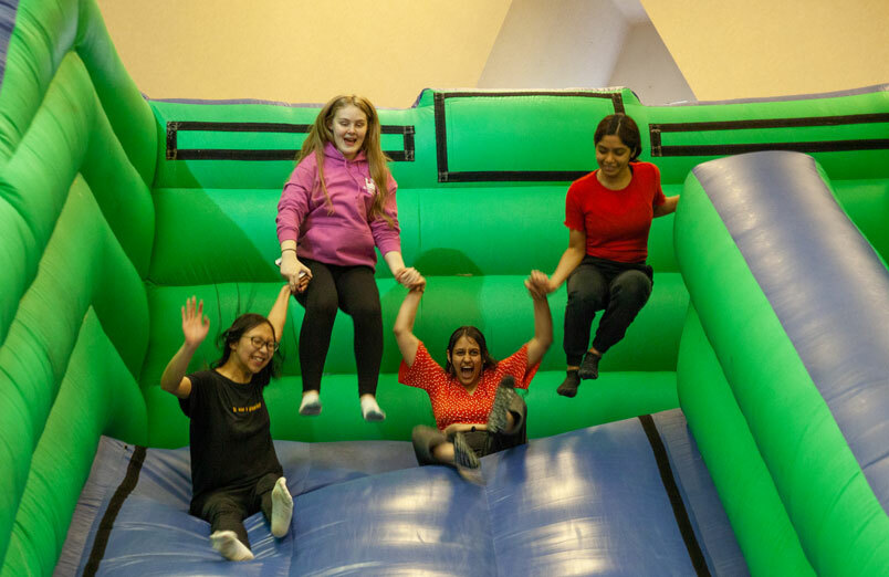 Four of St Margaret's Sixth Form Students bouncing on bouncy castle slide at party