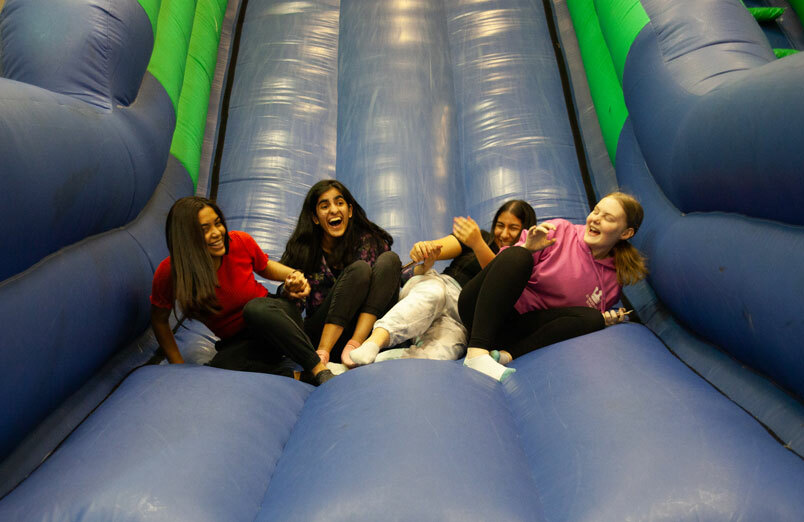 St Margaret's Sixth Form Students on bouncy castle at leaver's party
