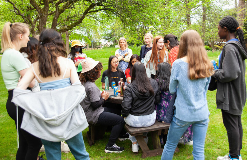 Group of St Margaret's Sixth Form pupils in orchard with the Head , Lara Péchard