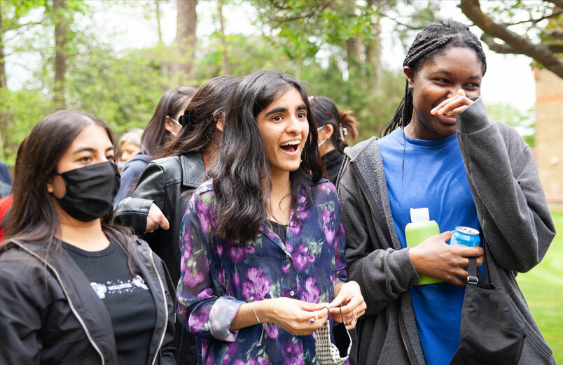 Three of St Margarets Sixth Form pupils laughing in orchard at Leaver's BBQ