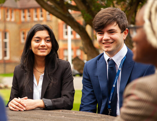 Sixth form pupils sitting and talking at table outside St Margaret's School