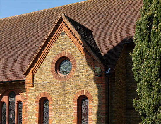 The roofline and circular stained glass window of the Waterhouse building at St Margaret's School in Bushey