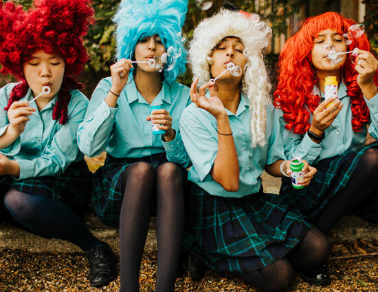 St Margaret's Senior School Pupils dressed in wigs and blowing bubbles for an art project