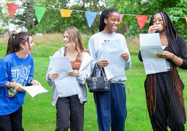 Four pupils laughing and opening GCSE results in orchard at St Margaret's School