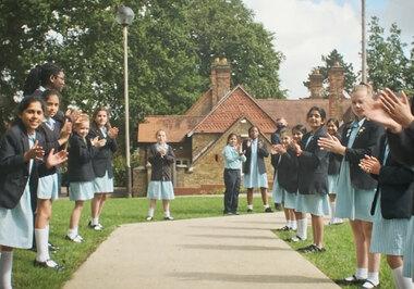 Junior School pupils clap their fellow Year 6 classmates up to Senio School