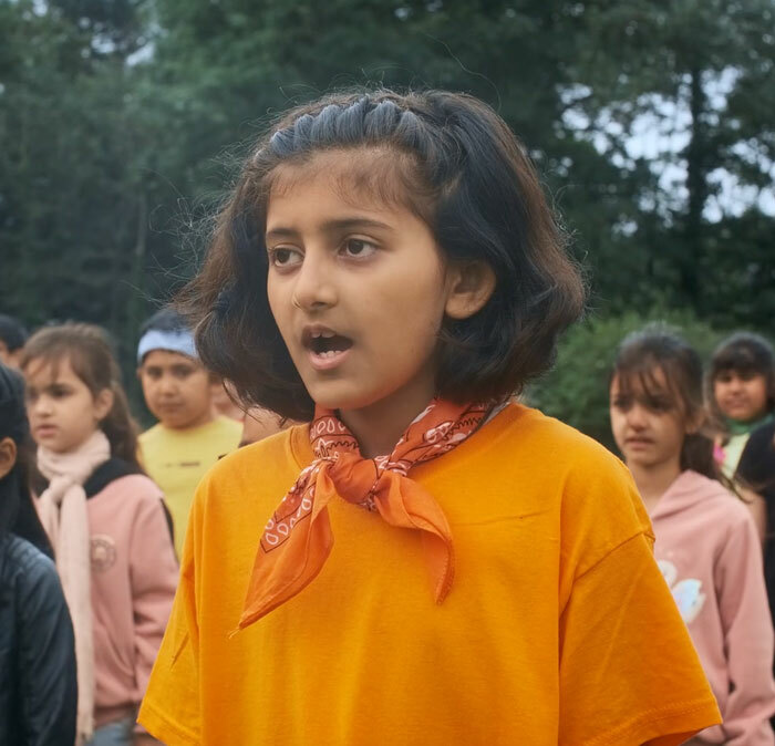 A St Margaret's Junior School pupil singing in the Believer music video