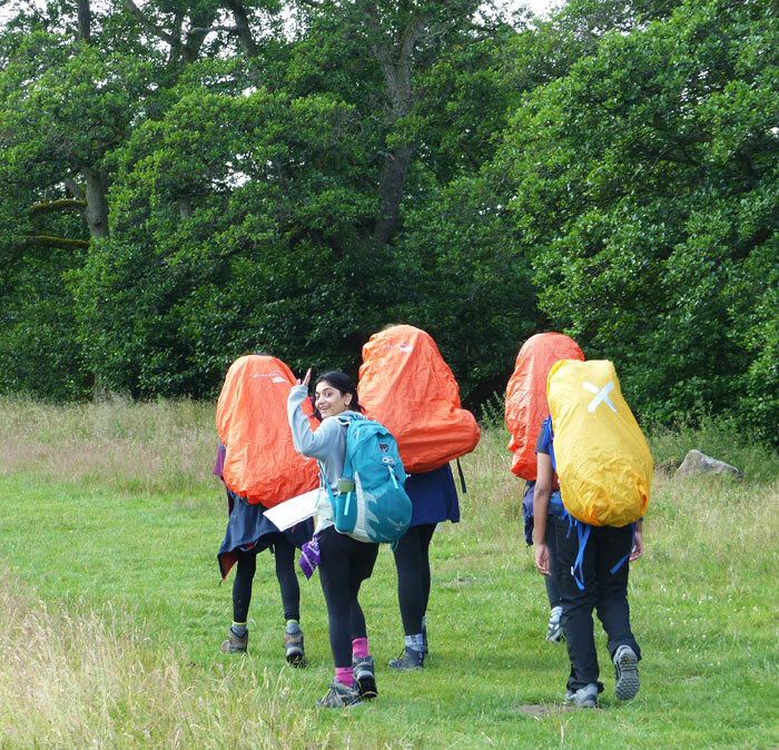 Girl waving whilst heading off with friends on Duke of Edinburgh's award expedition