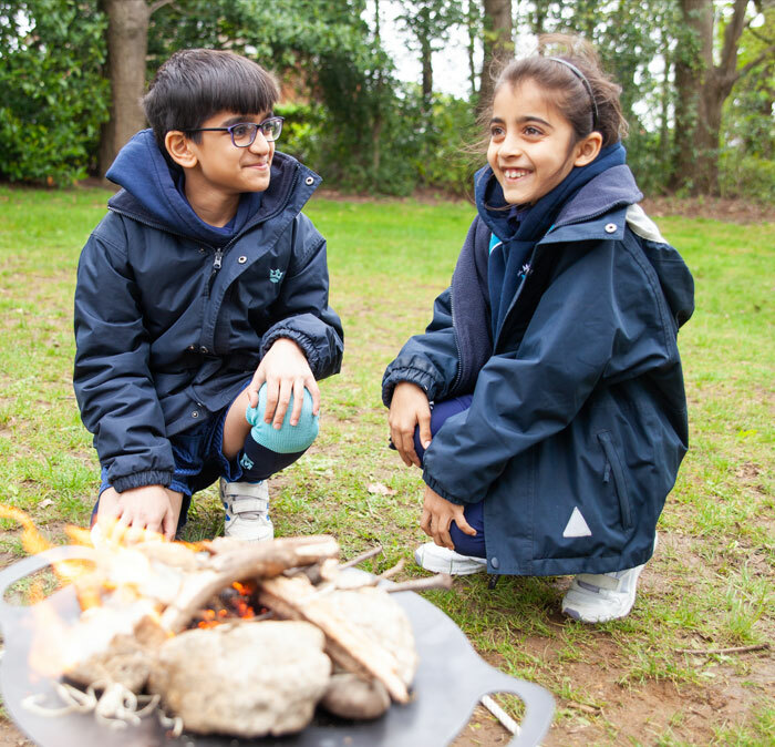 Two pupils from St Margaret's Junior School sat round a camp fire in an Outdoor Education lesson