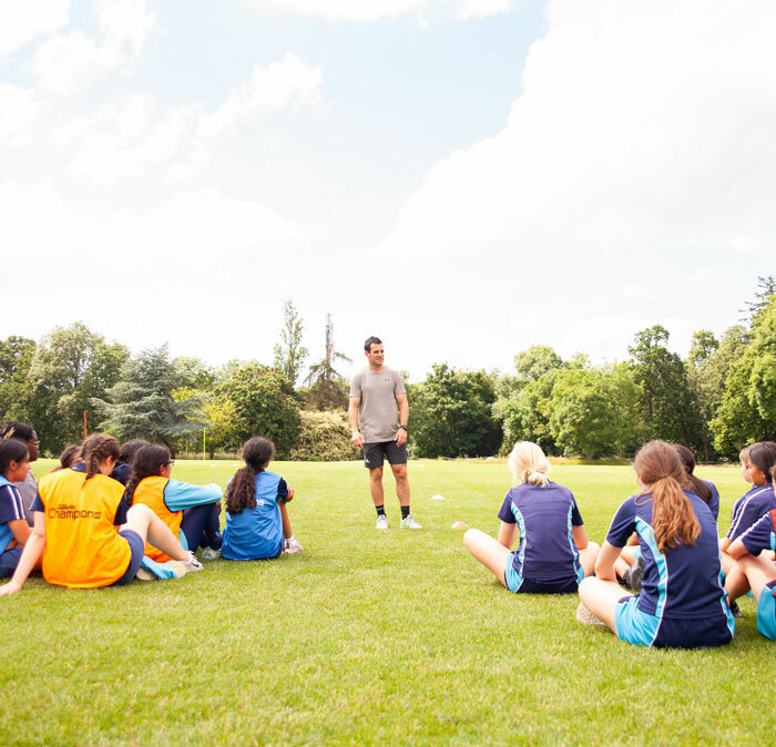 Group of St Margaret's Senior School pupils sitting on playing field during sports masterclass