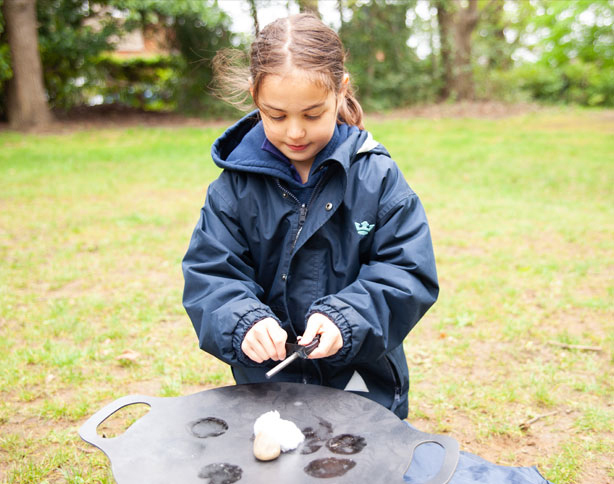 Young girl from St Margaret's Junior School trying to create a spark to light the fire pit